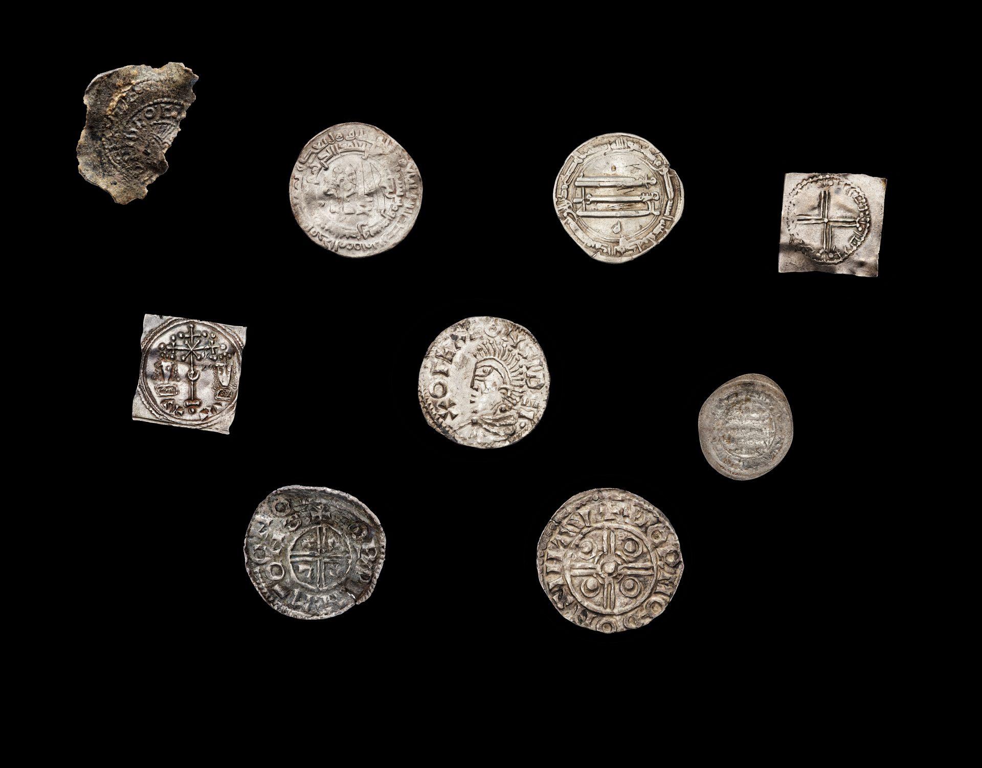 Mynt från vikingatiden mot svart bakgrund.